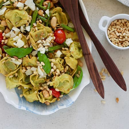 A platter with tortellini salad with a pair of serving spoons and a small pot of pine nuts