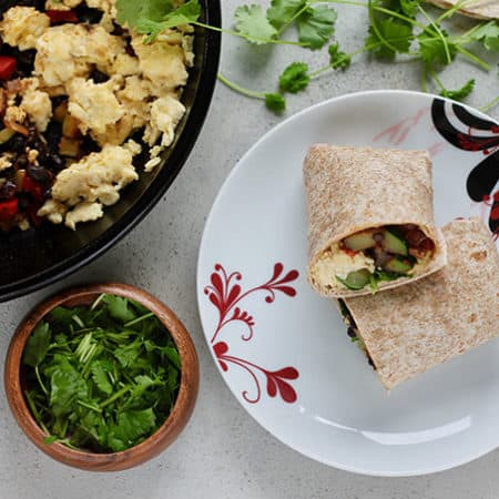 a vegetarian breakfast burrito cut in half on a white plate, with a skillet of breakfast burrito filling to the side