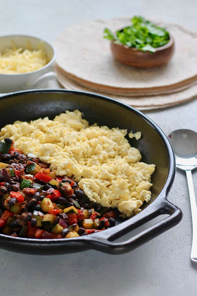 A cast iron skillet with mixed vegetables and black beans and scrambled eggs, a bowl of shredded cheese, cilantro, and a stack of whole wheat tortillas