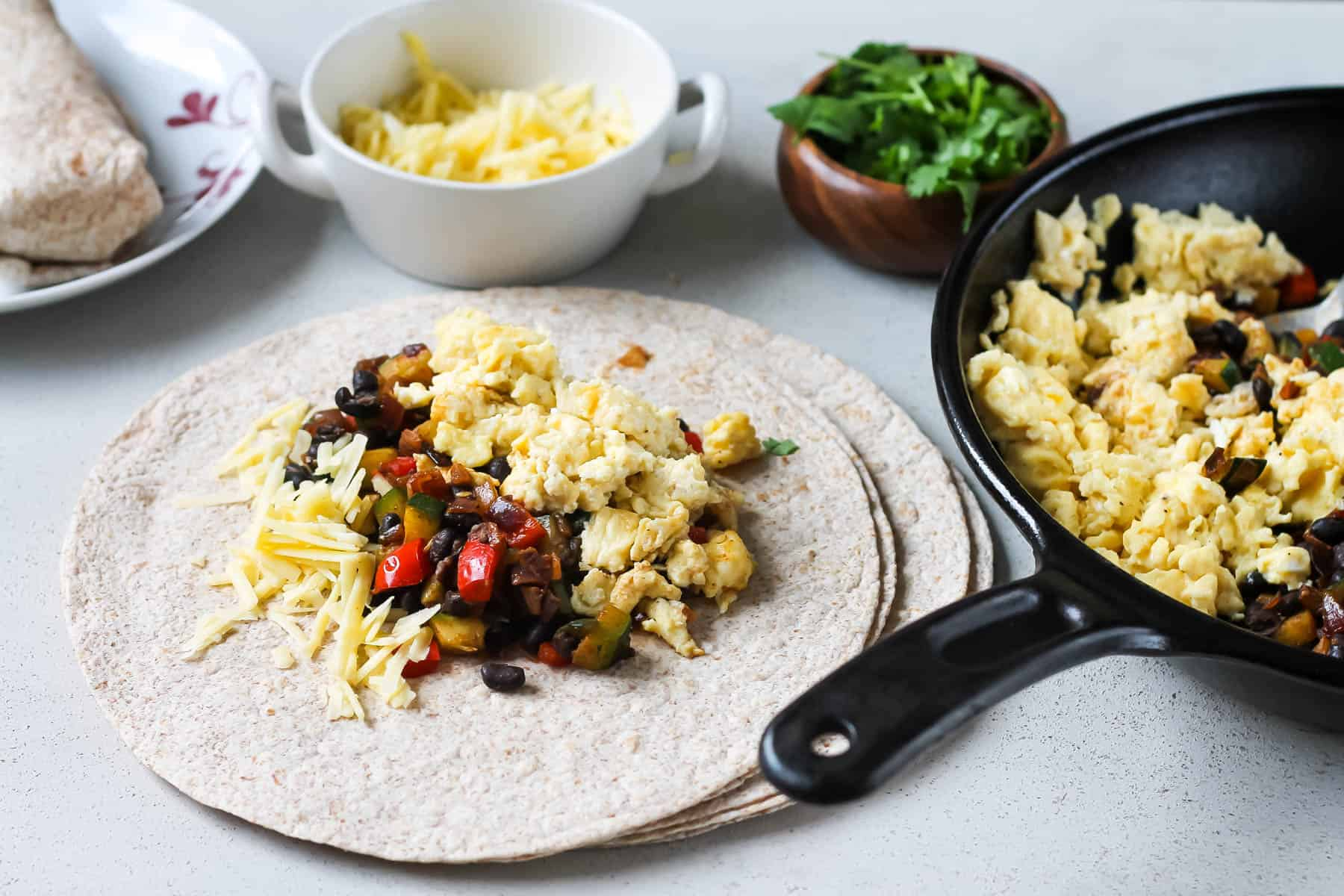 a whole wheat tortilla topped with scrambled eggs, vegetables, and beans