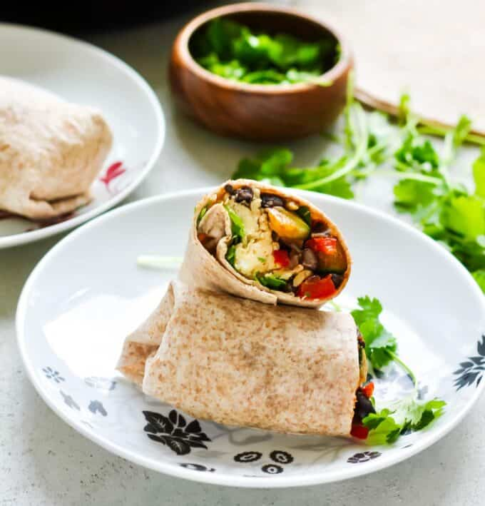 a vegetarian breakfast burrito on a white plate with cilantro in the background