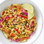 thai noodle salad in a white bowl with wedges of lime to the side