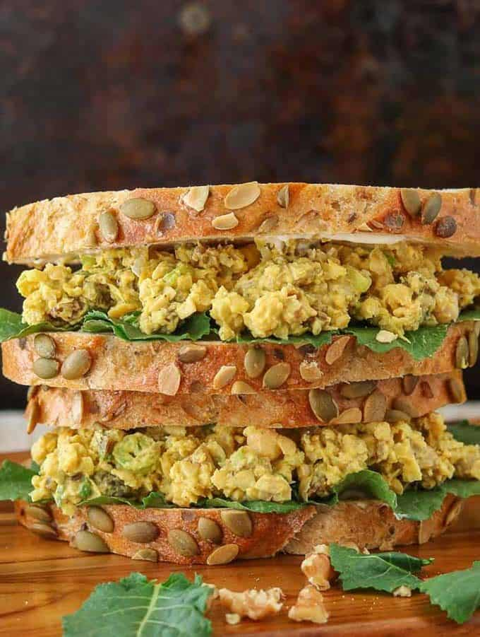 chickpea salad sandwich stacked against a black background