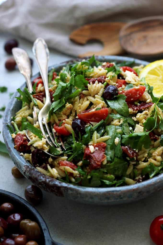 greek orzo salad in a dark grey bowl