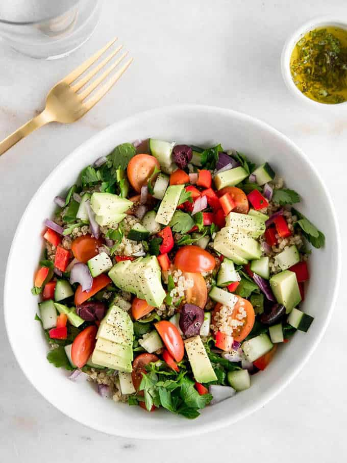 quinoa salad with cucumber and avocado in a white bowl