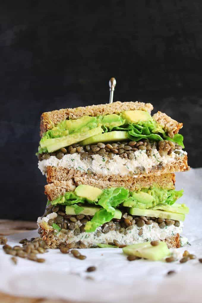 vegetarian sandwich with lentils, avocado, and ricotta against a black background