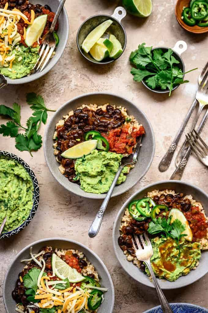 vegan burrito bowls with guacamole and cilantro on a grey background