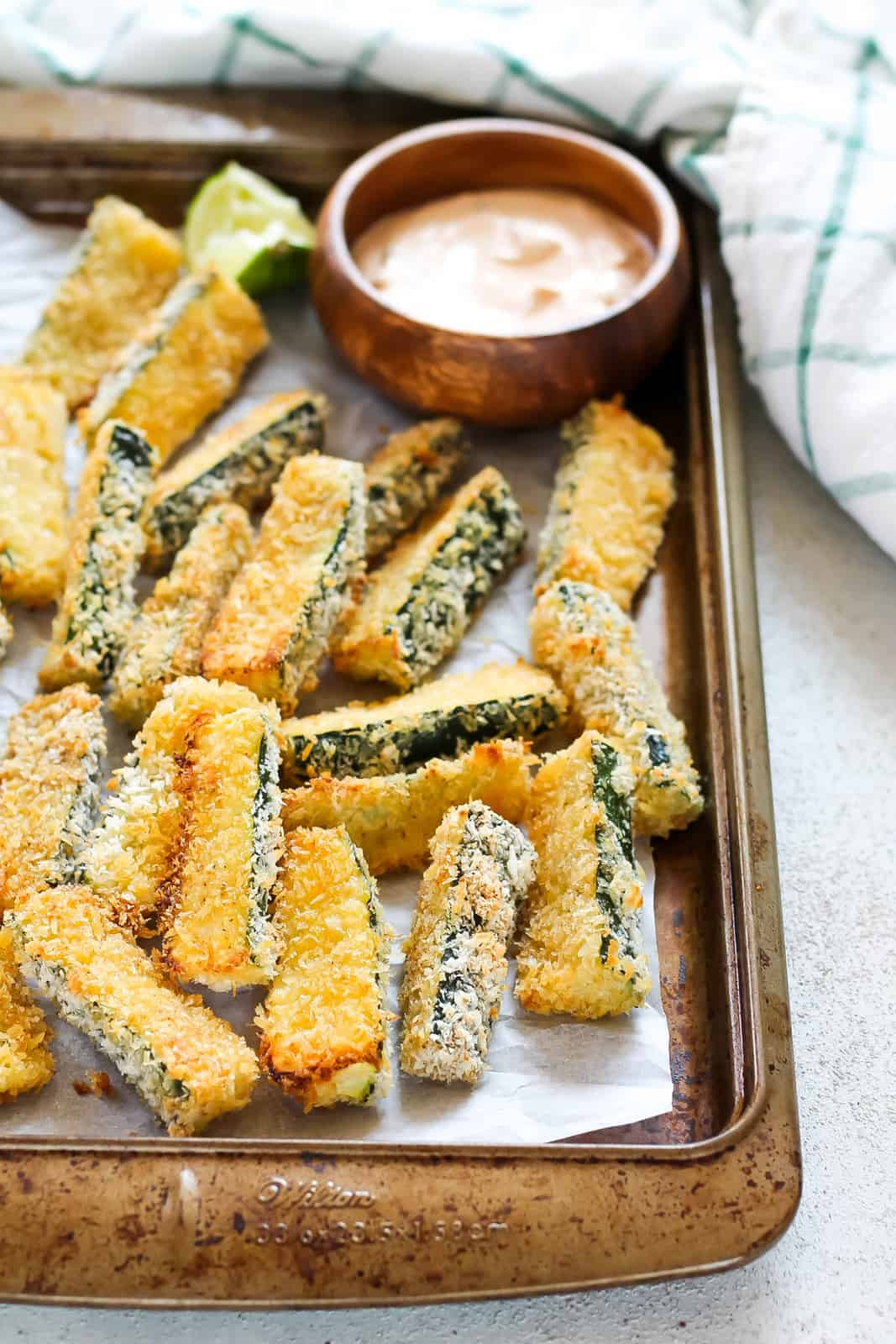 a tray of baked zucchini fries with a small bowl of dip and some lime wedges on the side