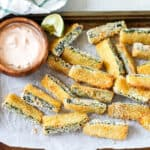 baked zucchini fries on a tray with a wooden bowl of dipping sauce on the side