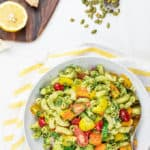 pesto pasta salad topped with tomatoes on a marble background
