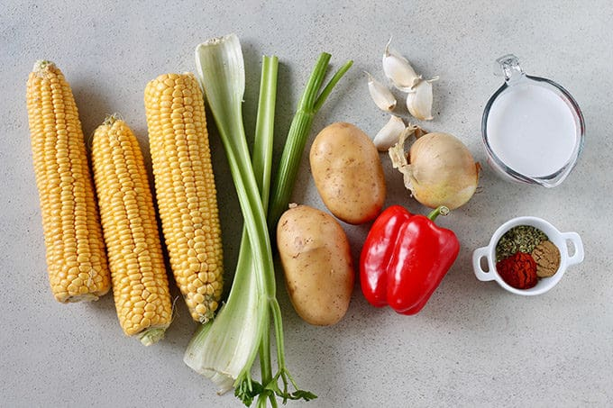 corn, celery, potatoes, garlic, red pepper, onions, coconut milk, spices on a grey background