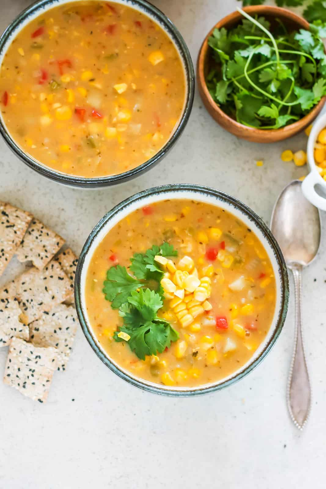 two grey and white bowls filled with vegan corn chowder and topped with corn and cilantro