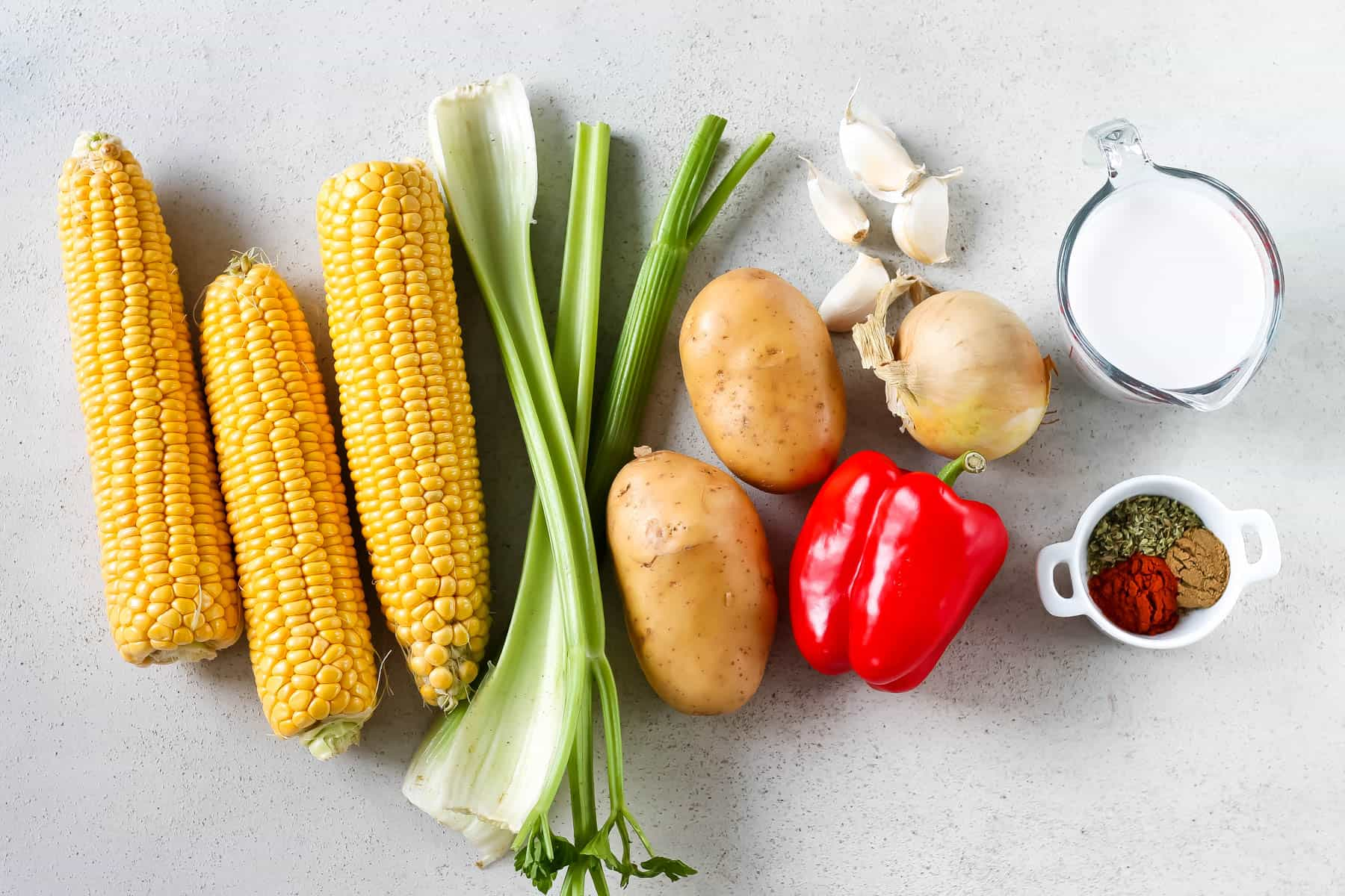 corn, celery, potatoes, red pepper, garlic, spices, and coconut milk on a grey background