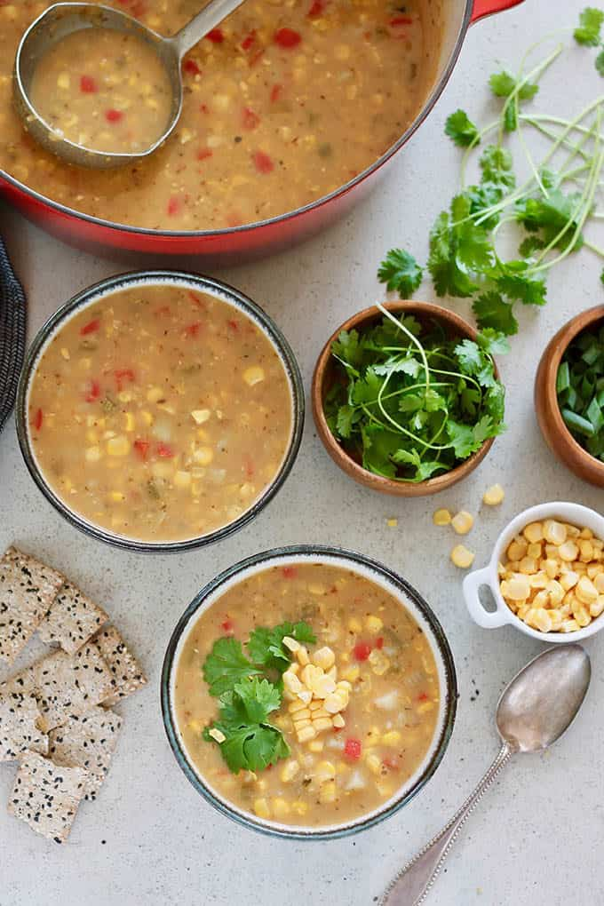 Two bowls of vegan corn chowder on a grey background with cilantro, corn kernels, crackers, and a silver spoon