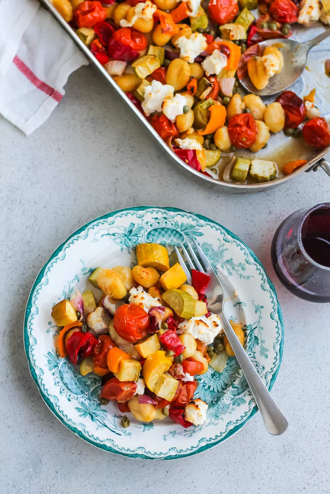 overhead photo of vegetarian gnocchi bake with zucchini and tomatoes on a blue patterned plate