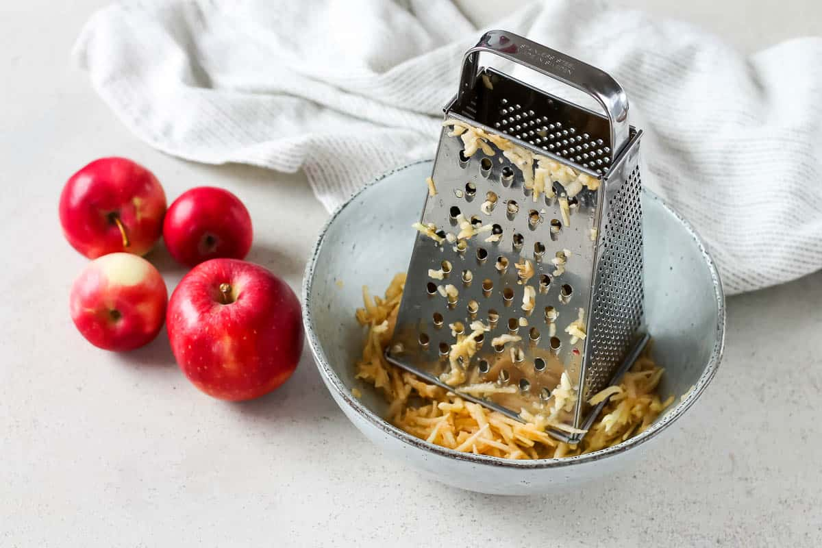 a blue bowl with grated apples and a metal grater