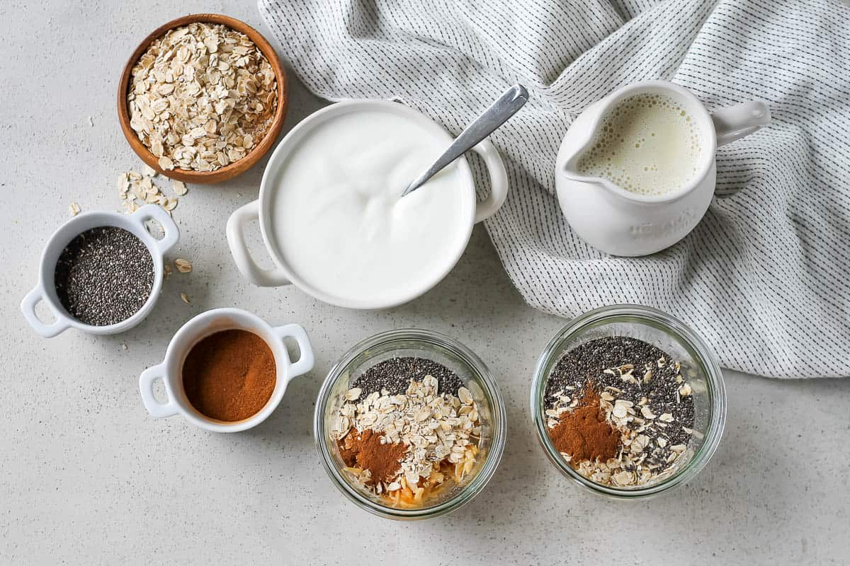 yogurt, oats, cinnamon, chia seeds, and some glass jars with overnight oats