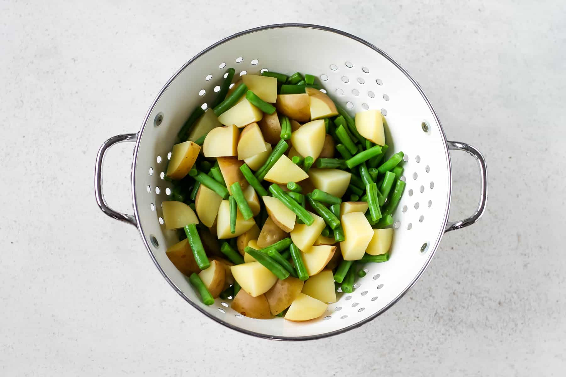 overhead photo of boiled potatoes and green beans in a white colander