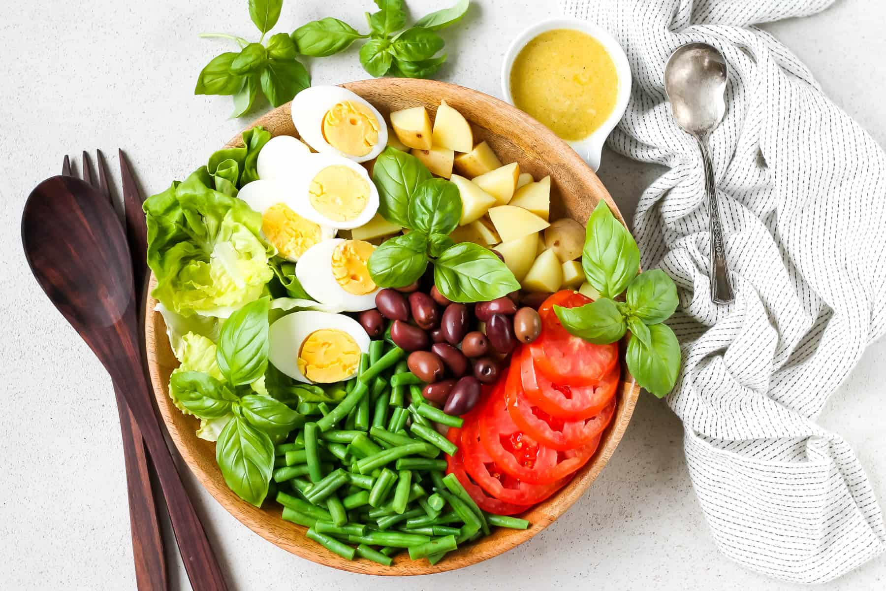 overhead photo of a vegetarian nicoise salad arranged in a wooden bowl with a small pot of dressing to the side