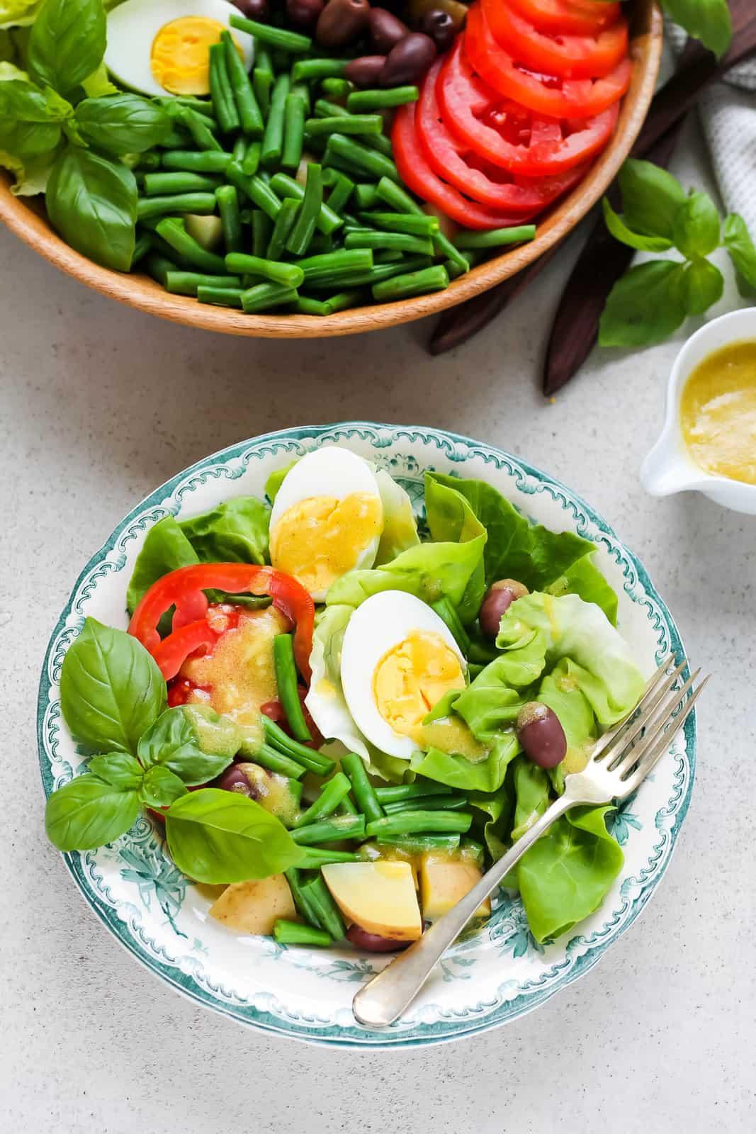 overhead photo of vegetarian nicoise salad on a blue plate