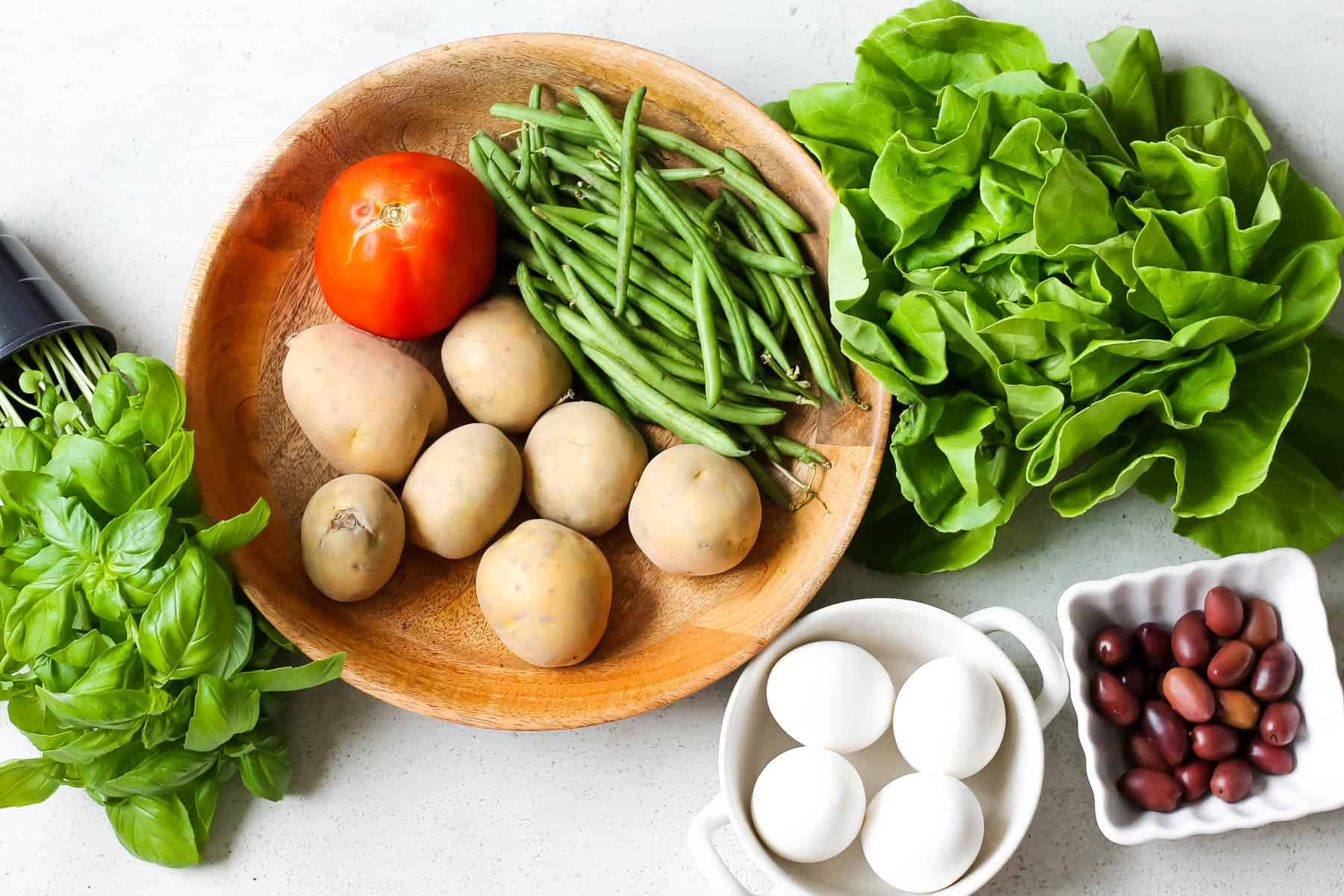 potatoes, green beans, and tomatoes in a wooden bowl surrounded by lettuce, olives, eggs, and basil on a grey background