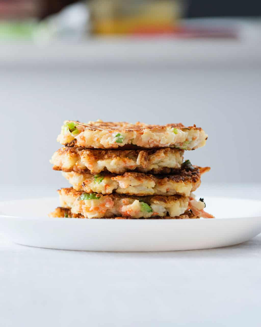 a stack of cauliflower and carrot fritters on a white plate