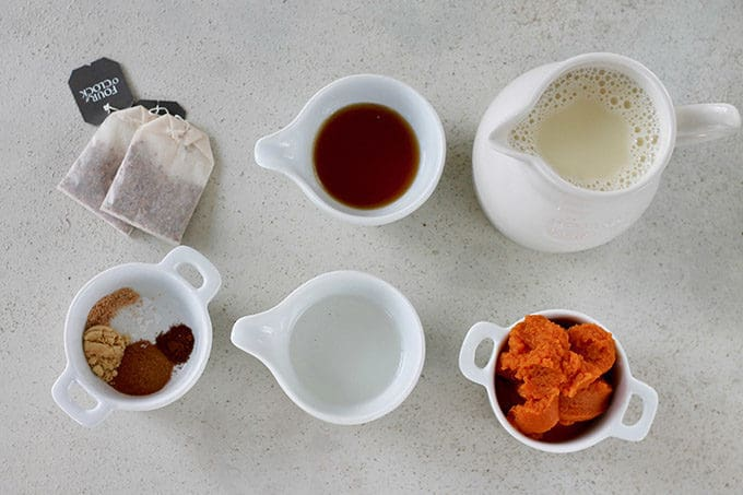 pumpkin, oat milk, maple syrup, mct oil, spices, and chai tea bags on a grey background