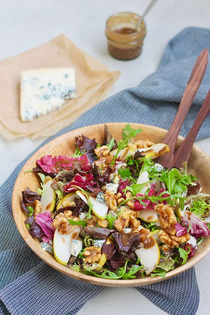 pear and gorgonzola salad in a wooden salad bowl with a black tea towel in the background