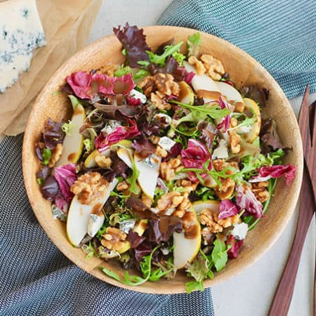 overhead photo of pear and gorgonzola salad on a grey background