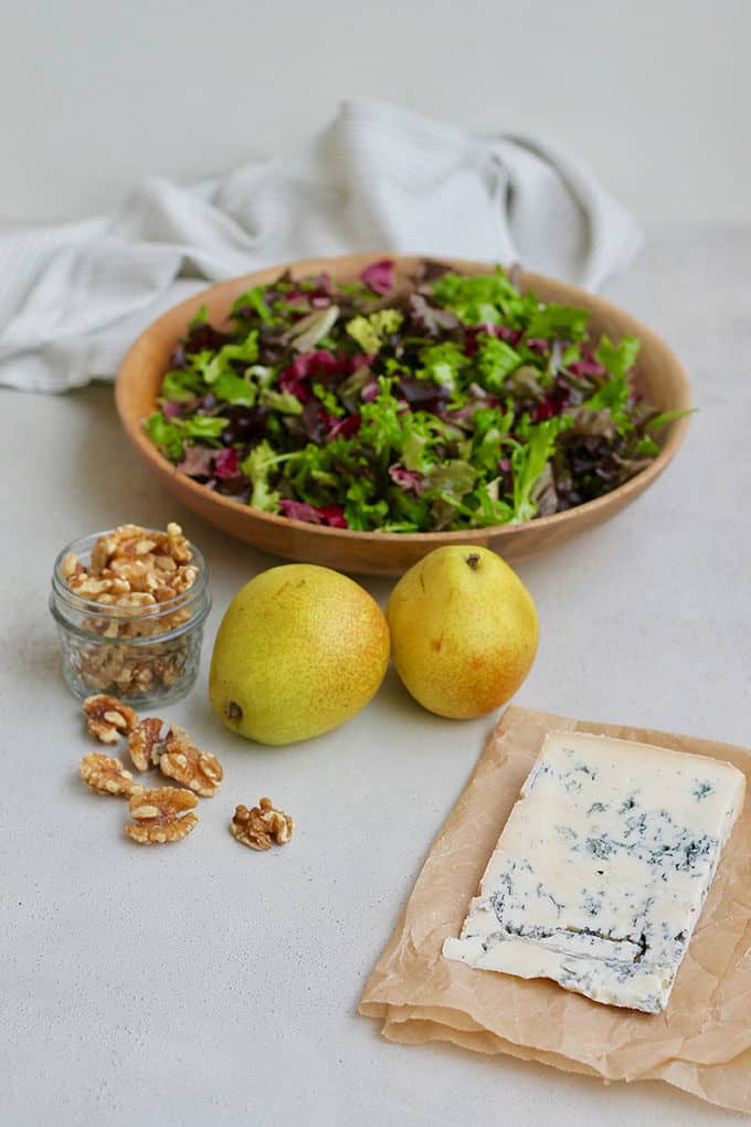 pear, lettuce, gorgonzola, and walnuts on a grey background