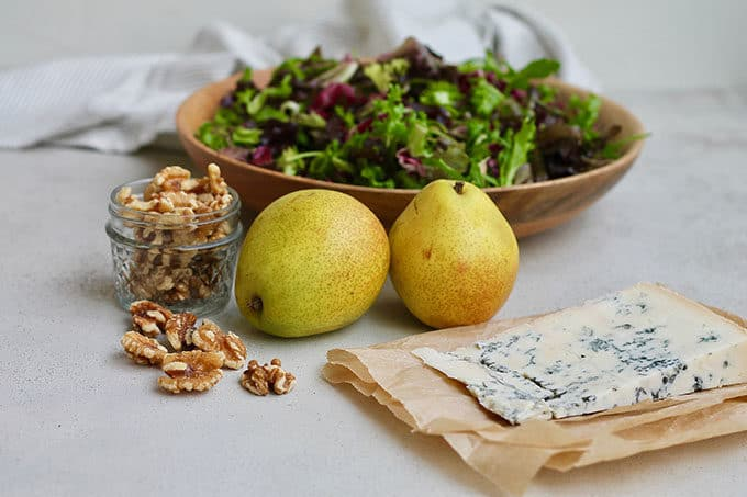 lettuce, walnuts, pears, and blue cheese on a grey background