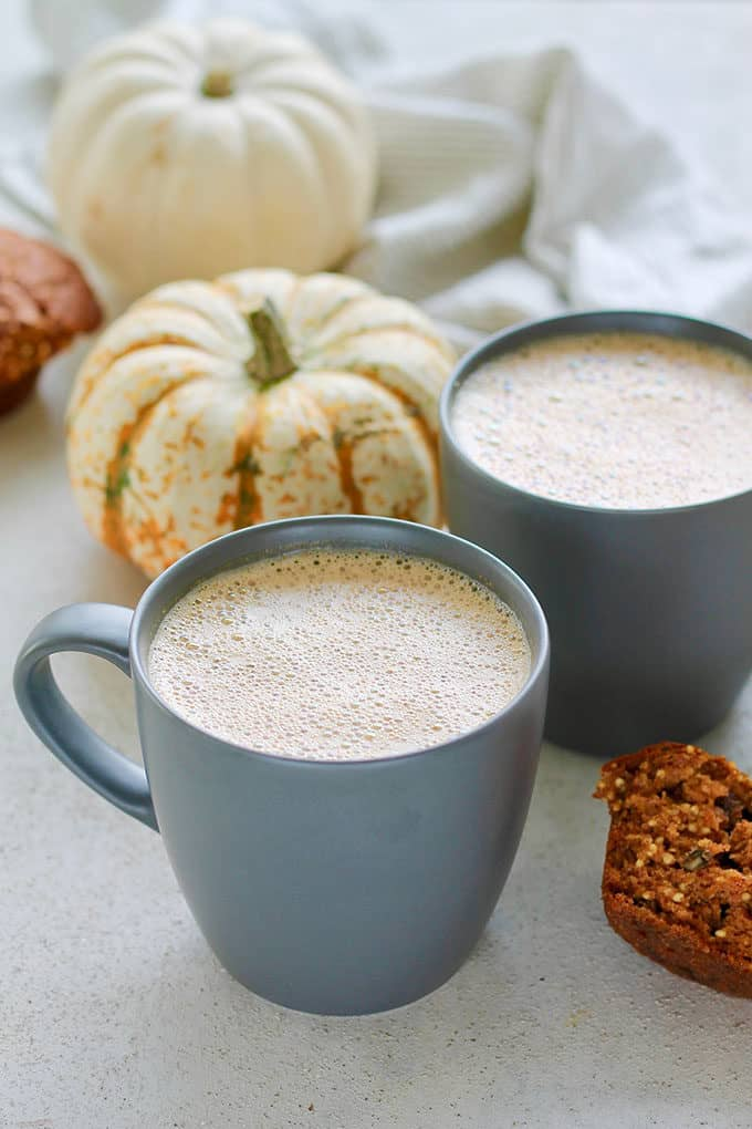 two mugs of pumpkin chai latte with a muffin and decorative pumpkins in the background
