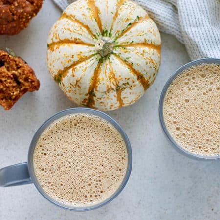 pumpkin chai lattes with a muffin and a decorative pumpkin