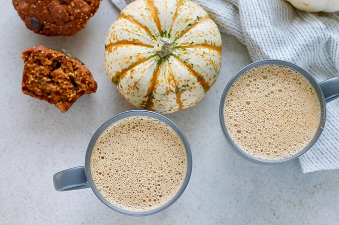 pumpkin chai lattes with a muffin and a decorative pumpkin
