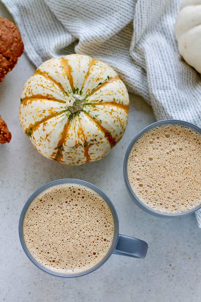 two pumpkin chai lattes on a grey background with ornamental pumpkins and a grey tea towel