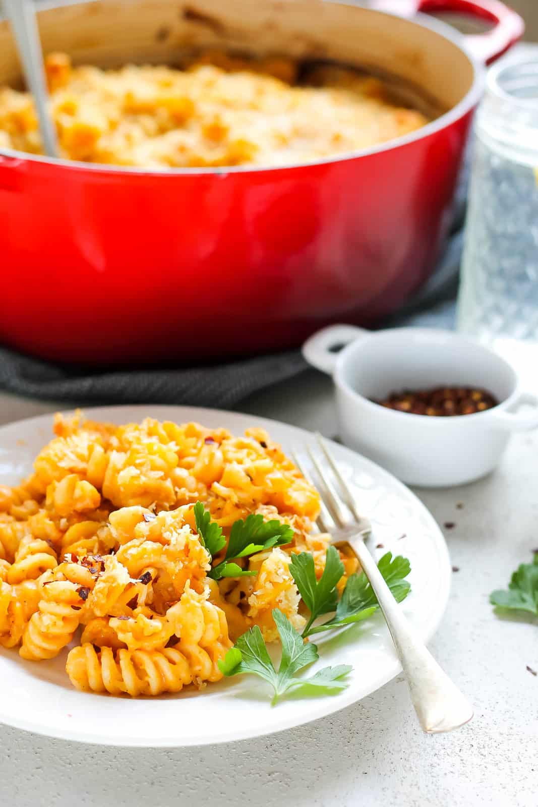 pumpkin mac and cheese on a white plate with a red casserole in the background