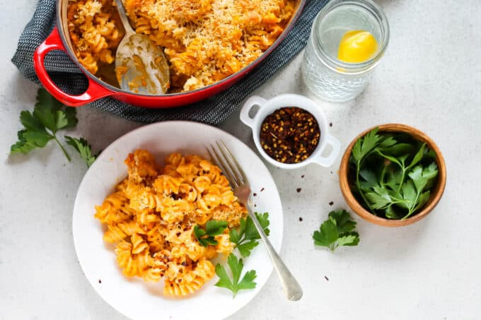 pumpkin mac and cheese on a white plate with a small wooden bowl of parsley to the side