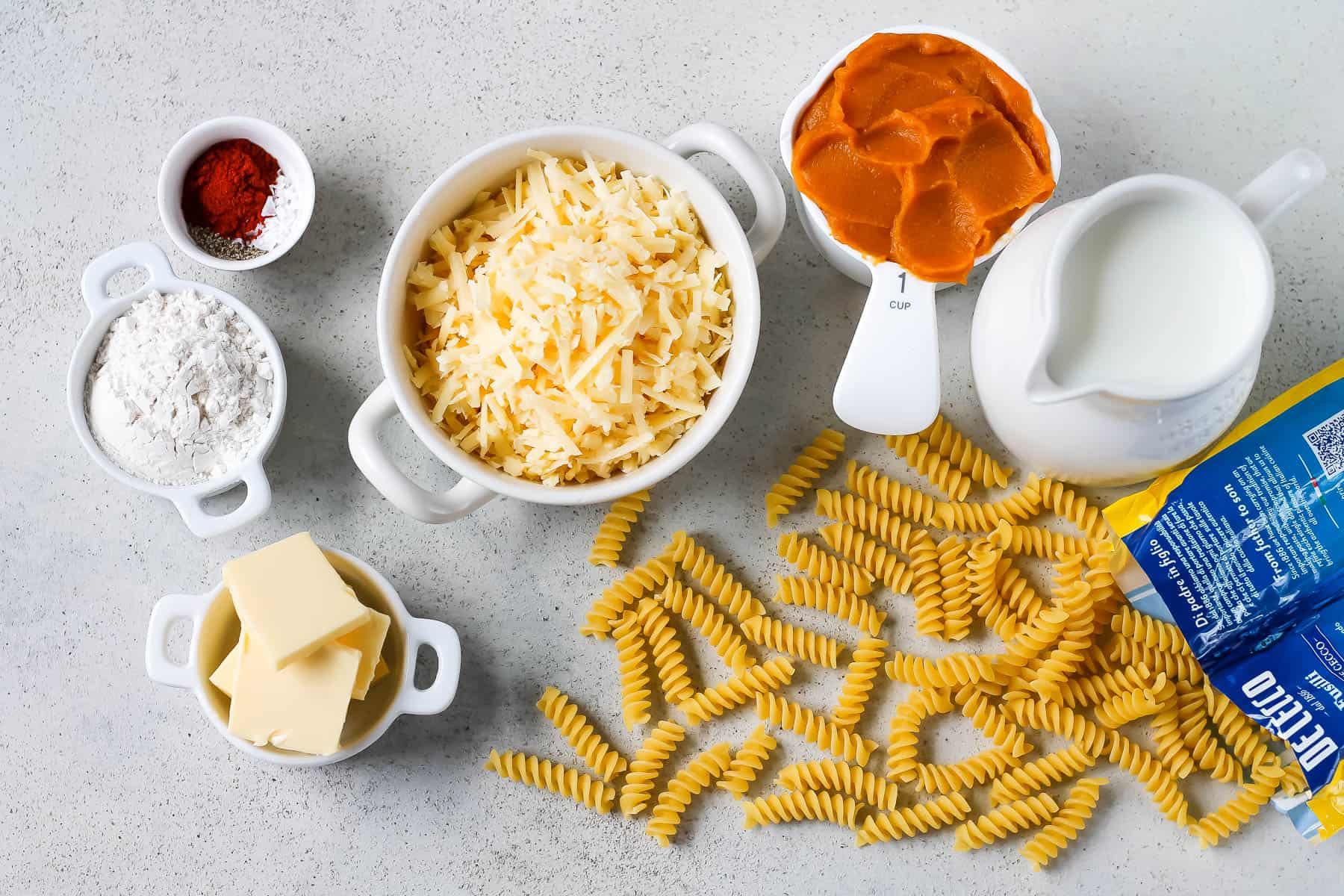 pasta, pumpkin puree, milk, cheese, butter, flour, and spices on a grey background