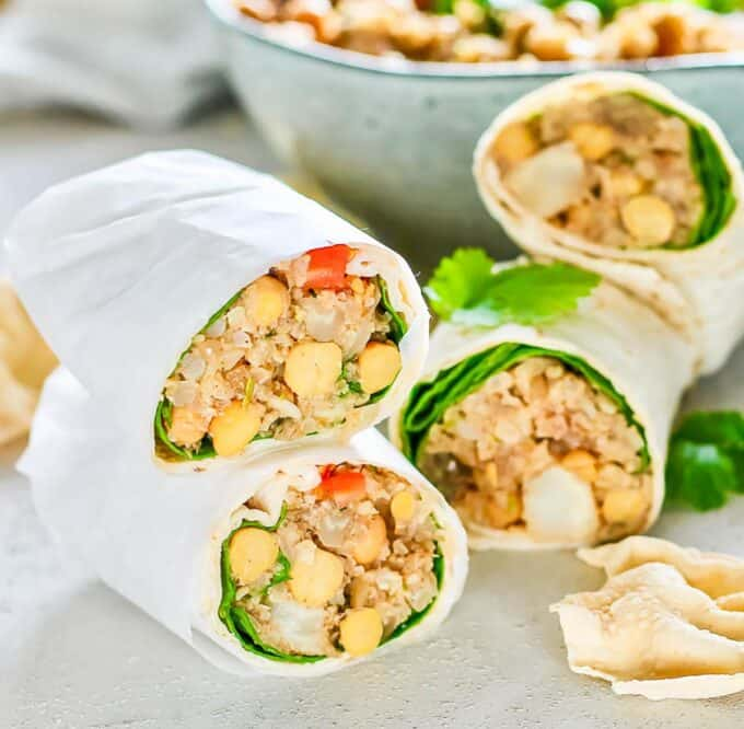 two curried cauliflower chickpea wraps wrapped in parchment paper and stacked up