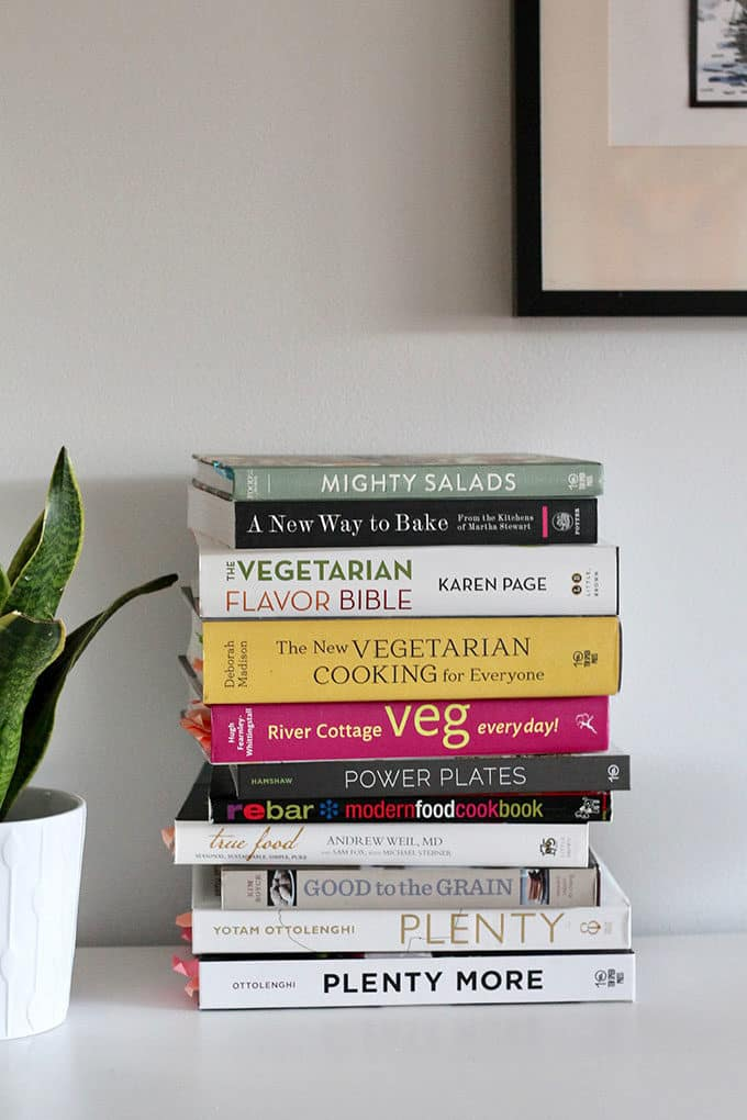 A stack of healthy cookbooks on a white table
