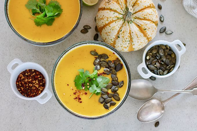 pumpkin curry soup on a grey background with pumpkin seeds and chili flakes scattered on top