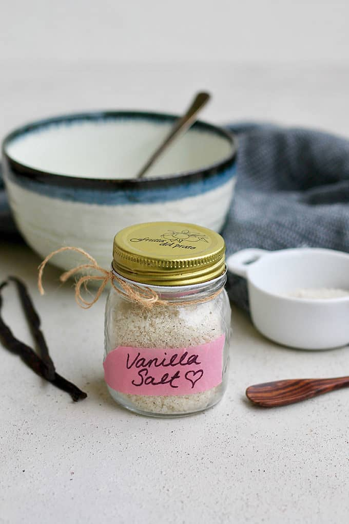 a small jar of vanilla salt with a pink label with vanilla beans in the background