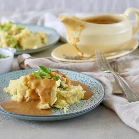 a blue plate of mashed potatoes topped with vegan gravy
