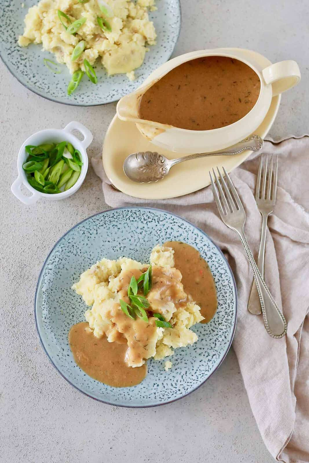 overhead photo of mashed potatoes topped with vegan gravy on a blue plate