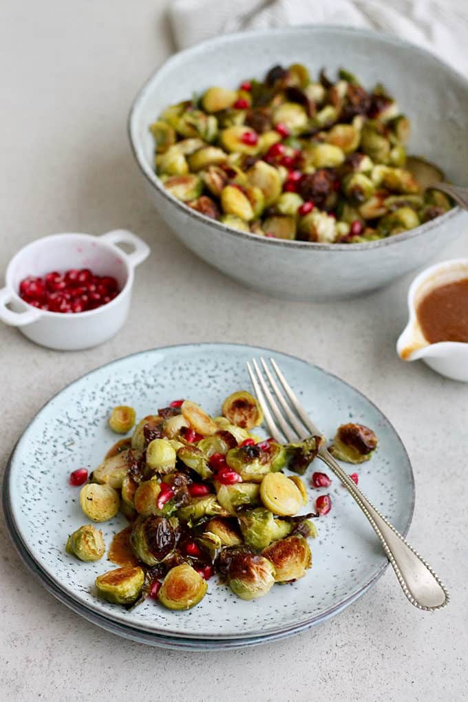 maple roasted brussels sprouts topped with pomegranate on a blue plate