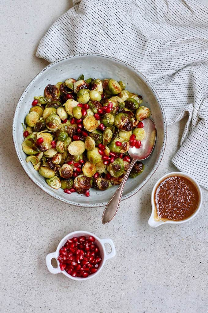 A bowl of maple roasted brussels sprouts with a small pot of dressing to the side