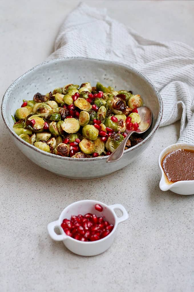 a blue serving dish with maple roasted brussels sprouts on a grey background
