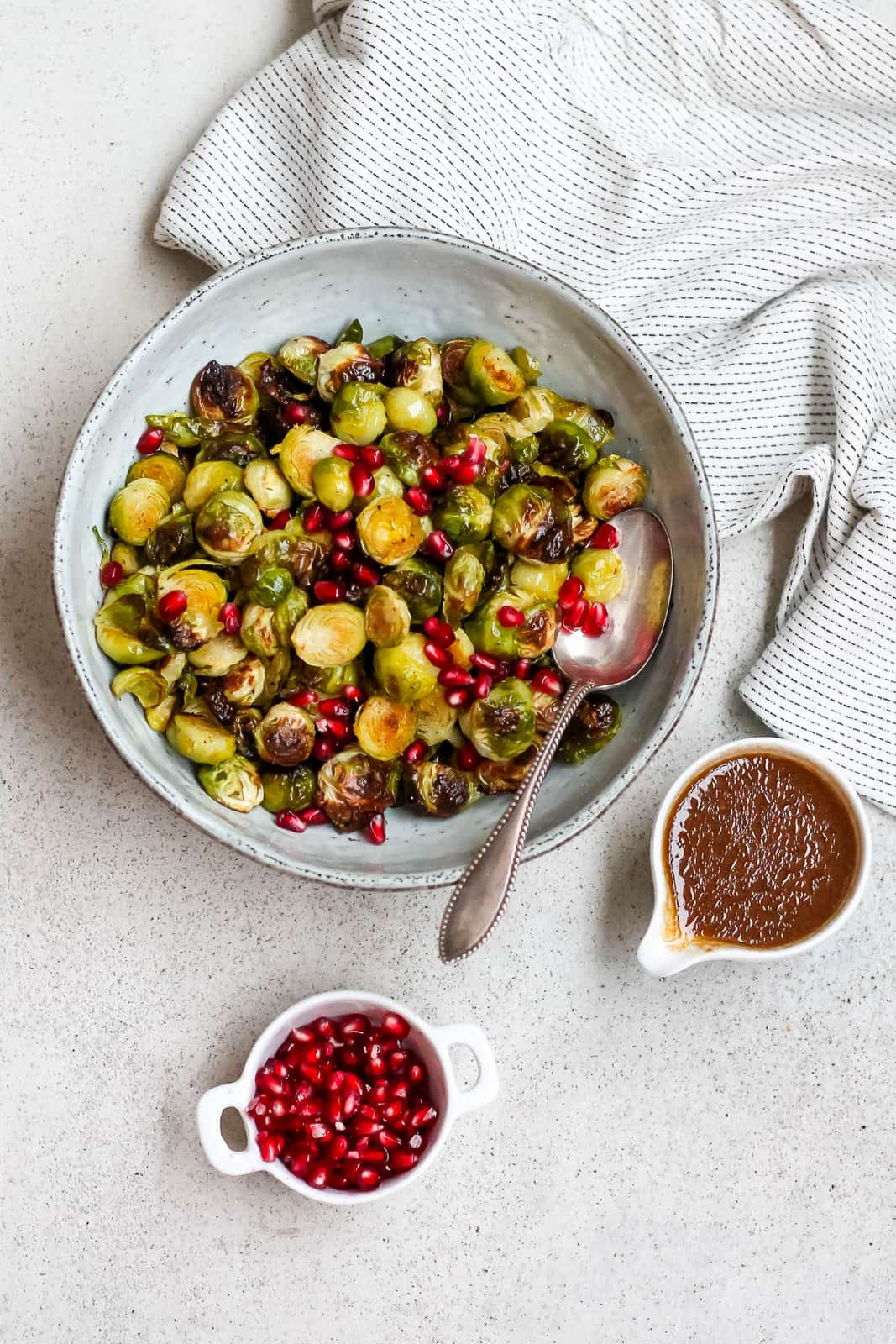 a blue bowl of roasted brussels sprouts with a white jug of dressing to the side