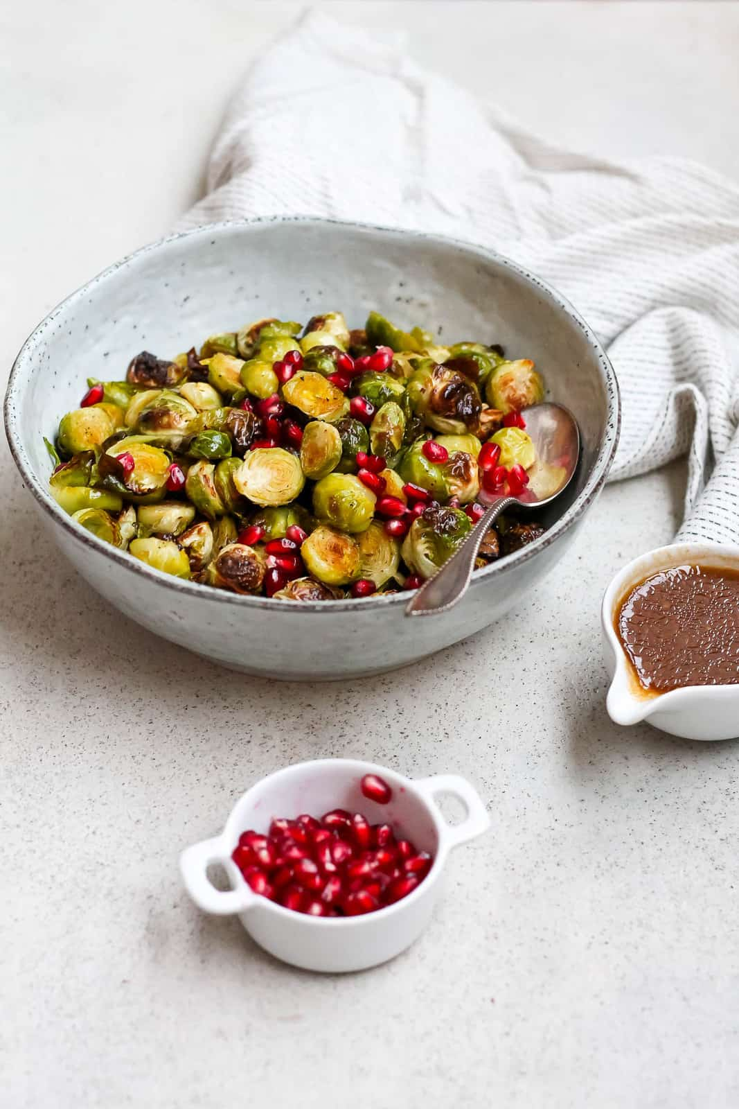 a blue bowl of roasted brussels sprouts with a white dish of pomegranate seeds in the front