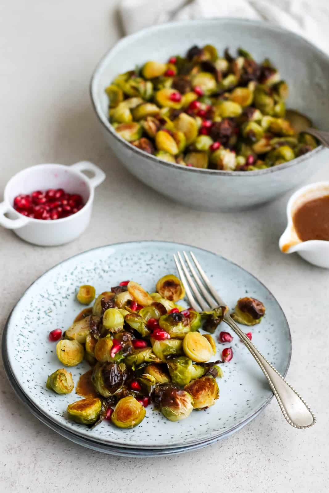 miso roasted brussels sprouts topped with pomegranate seeds on a blue plate